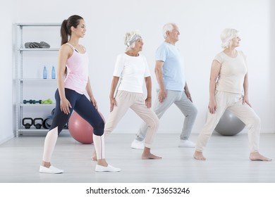 Young trainer and elderly people exercising during muscle-strengthening classes in room with balls
