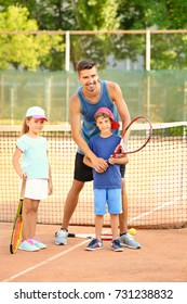 Young trainer with little children on tennis court