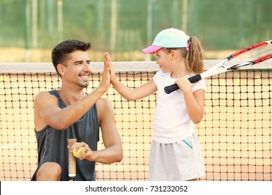 Young trainer with little girl on tennis court