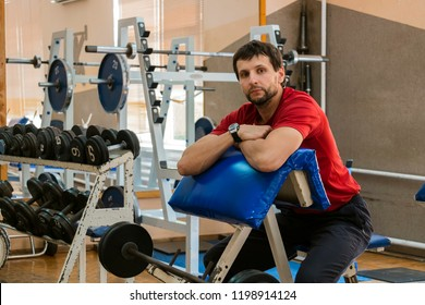 Young trainer in a simple small gym sits at the Scott bench