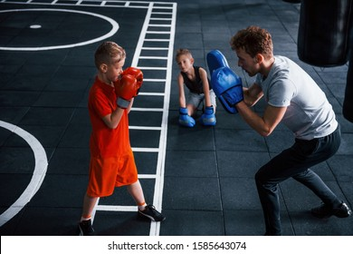 Young trainer teaches kids boxing sport in the gym.