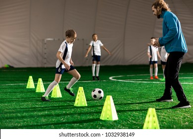 Young trainer and team of little boys playing or training on green lawn