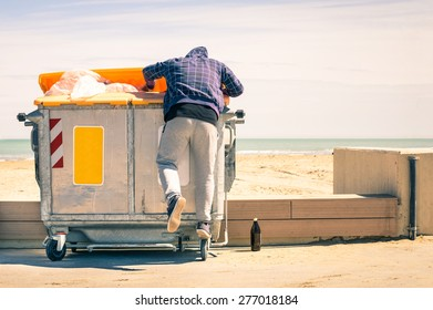 Young tramp rummaging in trash container looking for food and reusable goods - Modern concept of poverty with normal citizens becoming suddenly poor - Economy crisis and people with living issues