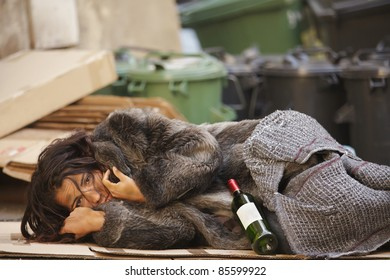 young tramp woman lying with bottle of wine  in bin