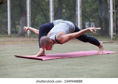 young tranquil woman doing high yoga lunge outdoor in summer park