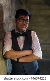Young transgender man in formal clothing poses in a grungy urban location