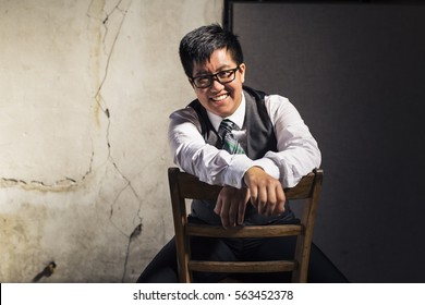 Young transgender man in shirt, vest, and tie in a grungy location