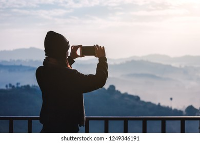 Young travel asian woman with sweater, mobile phone and Wool hat taking photo view of mountain and fog at morning in Khao Kho mountain, Phetchabun, Thailand, famous place in winter season
