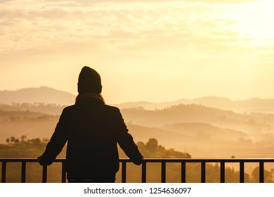Young travel asian woman with sweater and Wool hat look at view of mountain and fog at morning in Khao Kho mountain, Phetchabun, Thailand, famous place in winter season