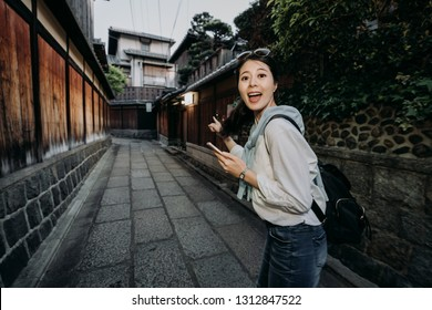young travel female backpacker cheerful holding cellphone online map finding destination pointing finger standing in Ishibe alley. girl tourist face camera smiling finding hotel in kyoto japan.