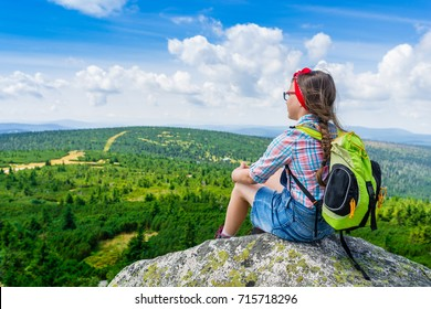 Young travel girl sitting on the rock mountain with backpack, relaxing - teen hiker girl relaxing and enjoying valley view