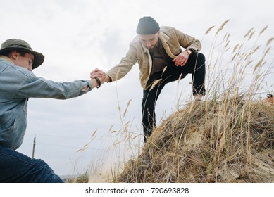 Young travel man lending a helping hand for friend in outdoor sandslope scenery.