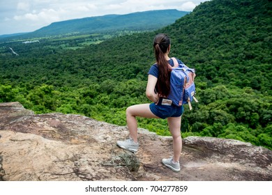 Young travel woman with backpack left leg on the rock look towards the mountains with lush forests and with the sky on the edge of the mountainside