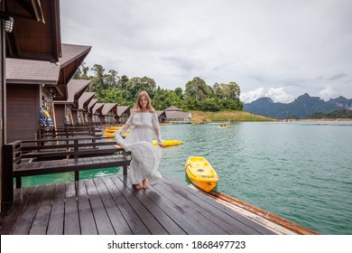 Young Travel Woman in White Dress Standing on Pier of Wooden House on Green Lake with Tropical Mountains. Female Tourist in Luxury Resort with Floating Raft Bungalows at Cheow Lan Lake, Thailand