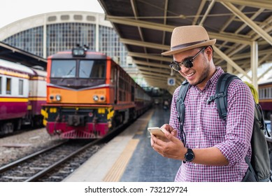 Young  traveler asian man texting smartphone while standing at train station