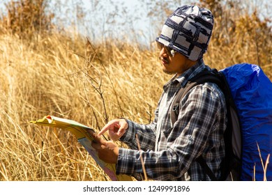 Young Traveler with backpack looking at the map for directions while hiking in mountain
