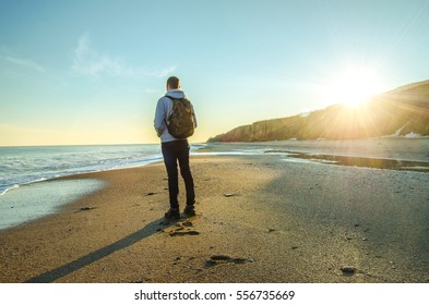 Young traveler with backpack stand on the beach of the sea near the mountains at the sunny day. Sunset. Travel theme