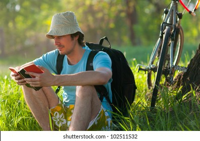 Young traveler with bicycle reading the book while resting in the forest on sunny spring day.
