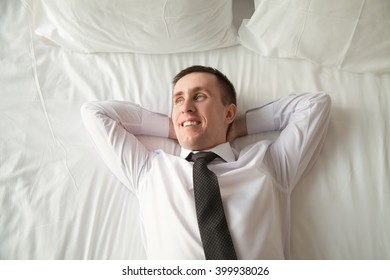 Young traveler businessman wearing white shirt and necktie lying on the bed in the hotel room with his hands behind head. Office worker relaxing after coming home with blissful expression