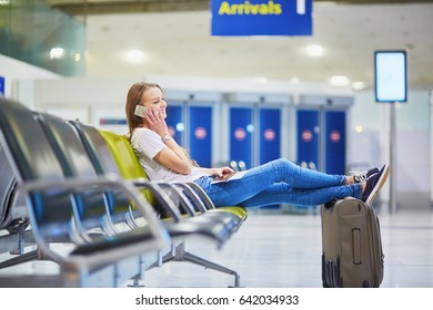 Young traveler with carry on luggage in international airport checking her mobile phone while waiting for her flight