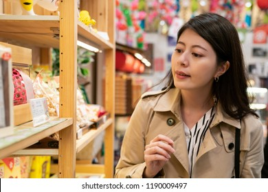 young traveler choosing souvenir in the local specialty shop in Japan, she wants to buy some delicious snack for her family