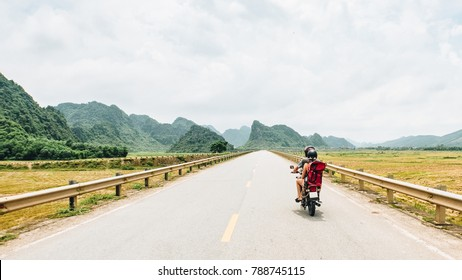 Young traveler couple making a adventure journey trip with a vintage motorcycle in Vietnam. Concept of best emotion and exploring different countries of a free backpacker life.
