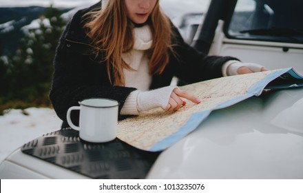 Young traveler girl searching right direction on map while traveling by authentic car in mountains, beautiful tourist woman with long hair exploring map while enjoying hot tea outdoor, winter vacation
