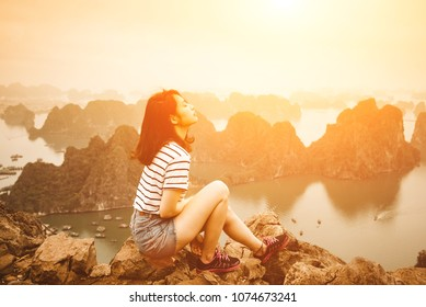 A young traveler girl sit on the top of mountain in Halong bay in sunset and enjoy the beauty of seascape. Young girl love wild life, travel, freedom.