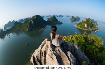 A young traveler girl sit on the top of mountain in Halong bay and enjoy the beauty of seascape. Young girl love wild life, travel, freedom.