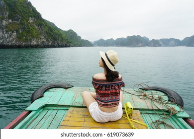 A young traveler girl sit on a boat go around Lan Ha bay, Cat Ba island and enjoy the beauty of seascape. Young girl love wild life, travel, freedom.