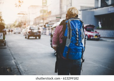 Young traveler hipster with backpack travel. Adventure tourism concept.