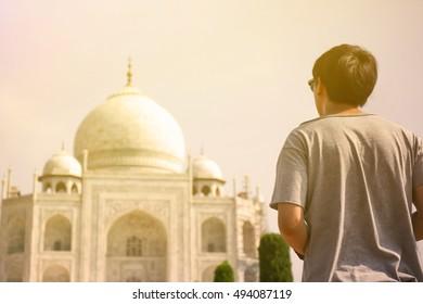 Young traveler looking and walking towards Taj Mahal in Agra, India.