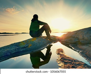 Young traveler man at magnificent sunset. Tourist  sitting on the cliff above the lake
