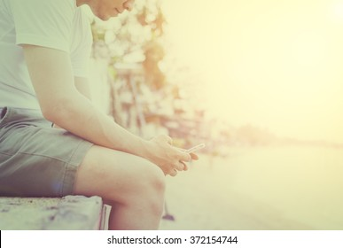 Young and traveler man sitting beside the sea and playing on his mobile phone