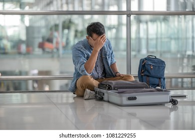 Young traveler man sitting on the floor at the terminal airport  finding something  lost . Unhappy man lost something on his trip,traveling concept.