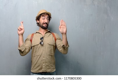 young traveler man or tourist smiling confidently while making a sincere promise or oath, solemnly swearing with one hand over heart.