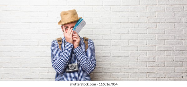 Young traveler man wearing backpack and a vintage camera feels worried and scared, looking and covering face, concept of fear and anxiety. Holding a boarding pass.