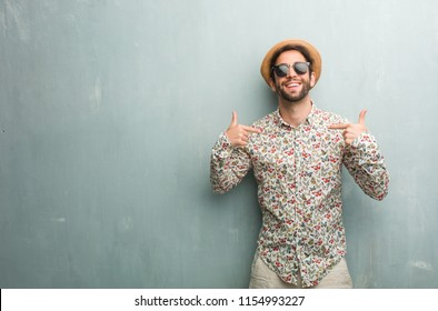 Young traveler man wearing a colorful shirt proud and confident, pointing fingers, example to follow, concept of satisfaction, arrogance and health