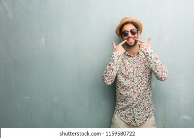 Young traveler man wearing a colorful shirt smiles, pointing mouth, concept of perfect teeth, white teeth, has a cheerful and jovial attitude