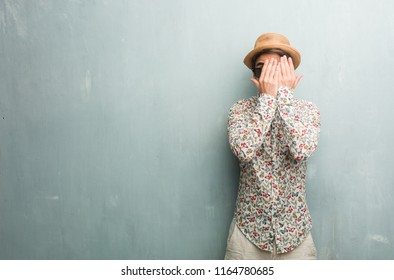 Young traveler man wearing a colorful shirt feels worried and scared, looking and covering face, concept of fear and anxiety