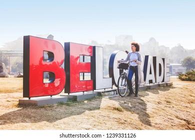 Young traveler mixed race woman with rent bike tourist visit Belgrade, Serbia, Europe.