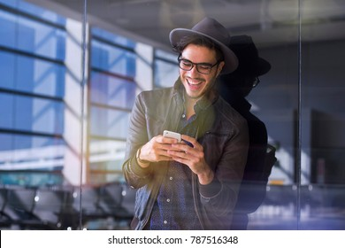 Young traveler on an airport, with a leather jacket texting with his smartphone