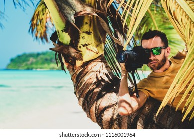 Young traveler on the holiday. Photographer with professional camera make photo from palm tree