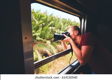 Young traveler on the holiday. Photographer with dslr camera photoshooting from open window of the vintage train.