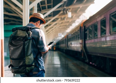 Young traveler on railroad station using phone in train station,copy space.