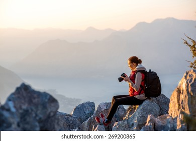 Young traveler photographer with photo camera and backpack sitting on the top of mountain and looking on the sunset