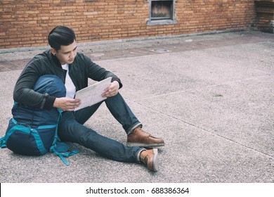 young traveler reading map. handsome asian man wearing black jacket and blue jeans sitting near old orange brick wall with backpack