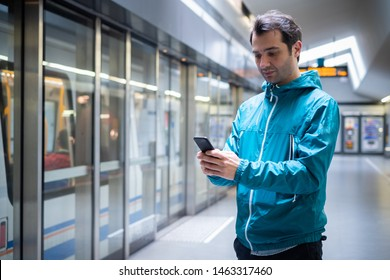 Young traveler reading social network on cell phone on subway metro public transport