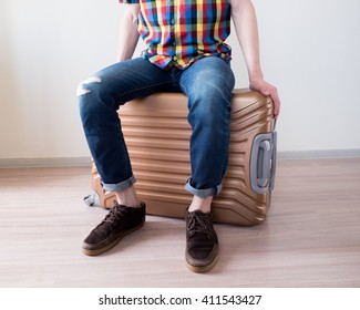 Young traveler sitting on big and heavy golden luggage for vacation
