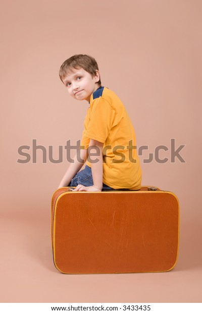 Young traveler sitting on suitcase isolated on beige background